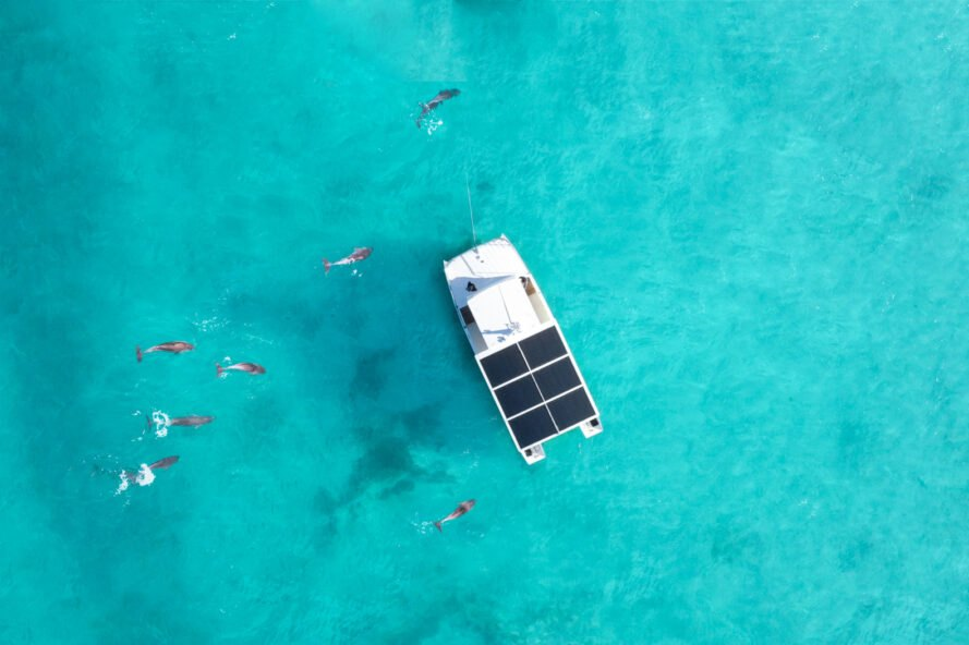 aerial view of white boat with solar-panels in clear blue water