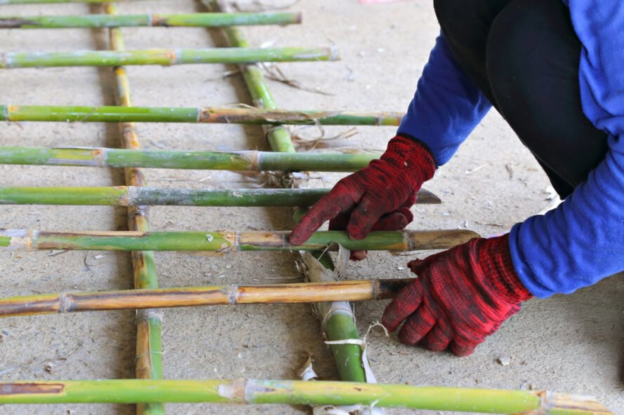 person putting together bamboo reinforcing for concrete