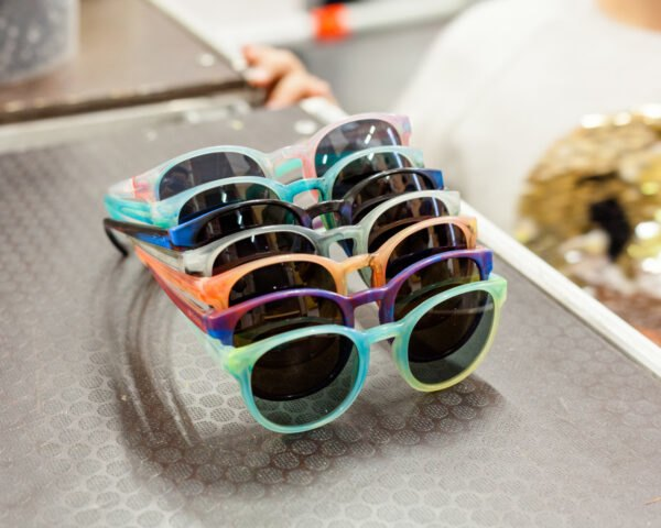 fos sunglasses in various bright colors on a table top