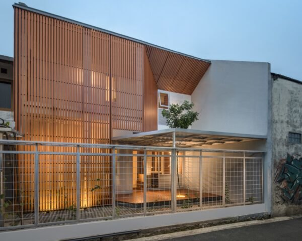 outdoor lights illuminate the timber home in the evening