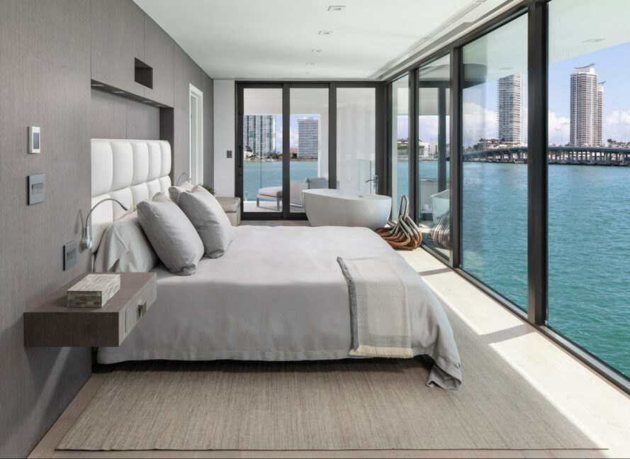 a bedroom with all glass facade looking out over water