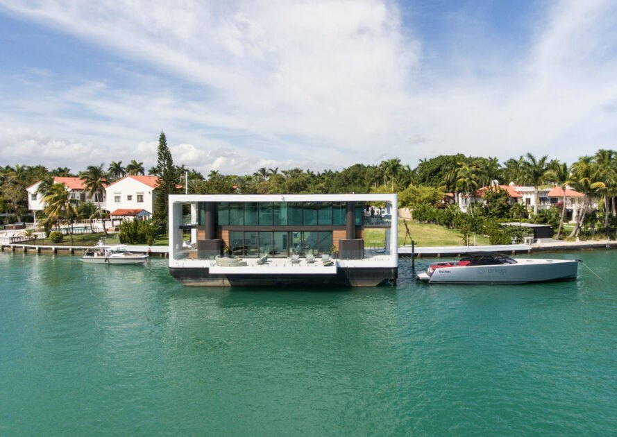 white home with glass facade floating on water in Miami