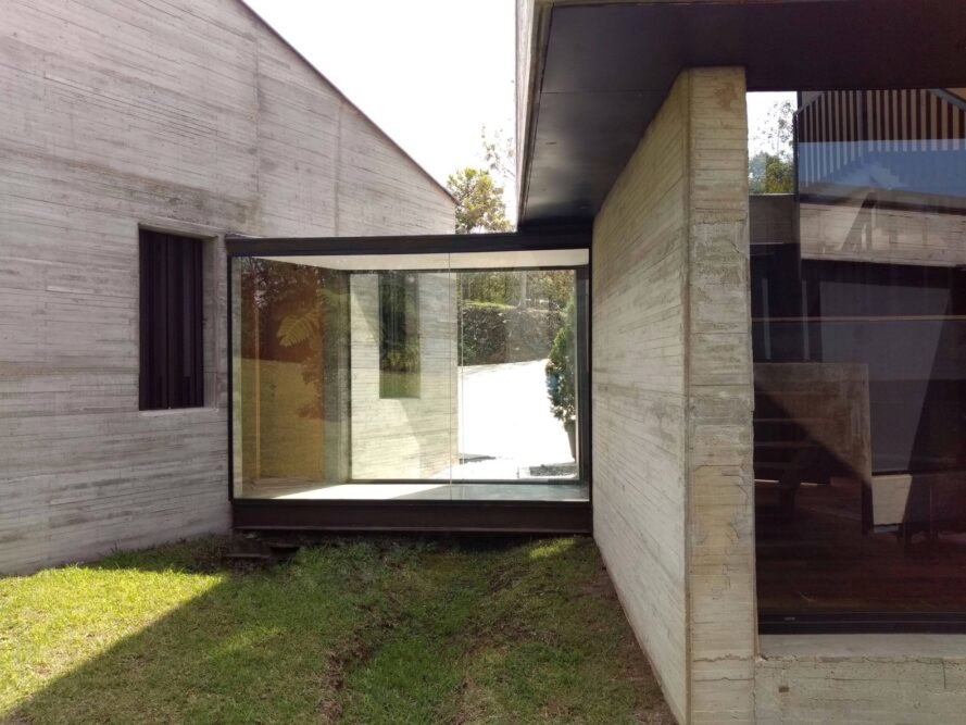 glass-enclosed hallway between concrete homes