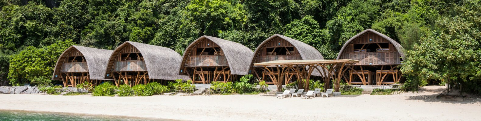 series of thatched roof huts on a remote beach