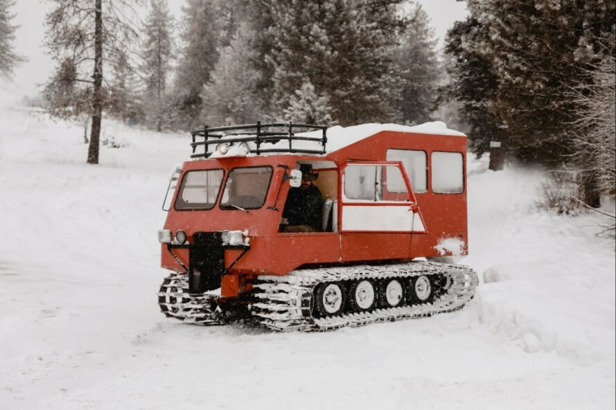 a red snowcat vehicle sitting in snow
