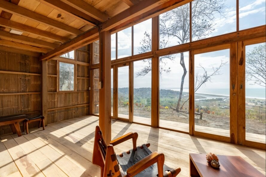 wood-lined room with chairs facing a glass wall with views of the sea