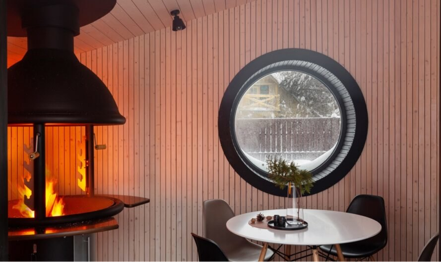 interior of tiny home with small rounded window near round dining table