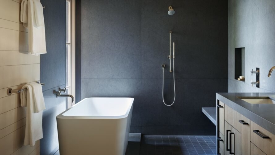 bathroom with isolated tub and dark colored walls