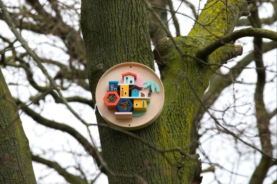 a colorful birdhouse tacked to a tree
