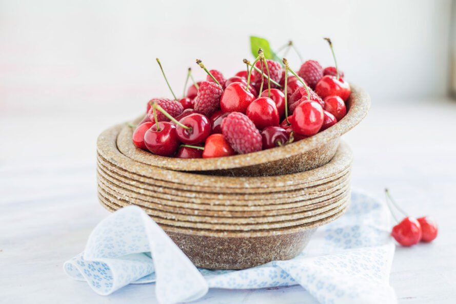 brown biodegradable tableware with bright cherries on plate
