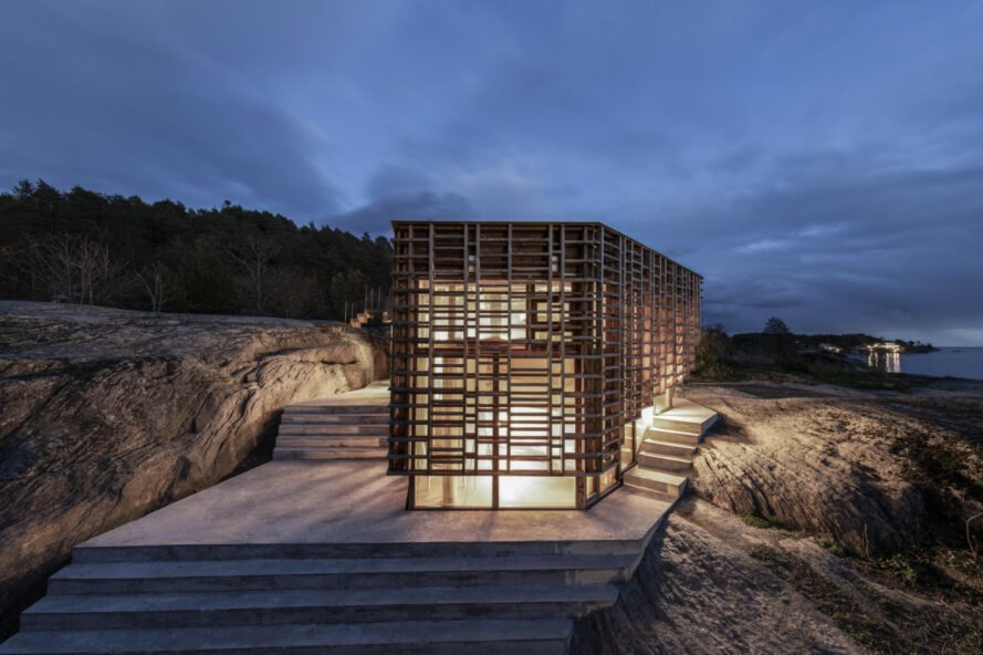 home wrapped in timber slats on concrete base all lit up at night