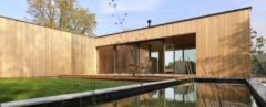 timber home lined with grass and a nearby natural pool