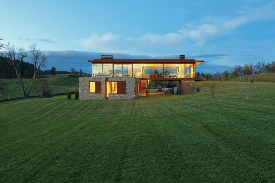 link farm house atop a grassy knoll during sunset