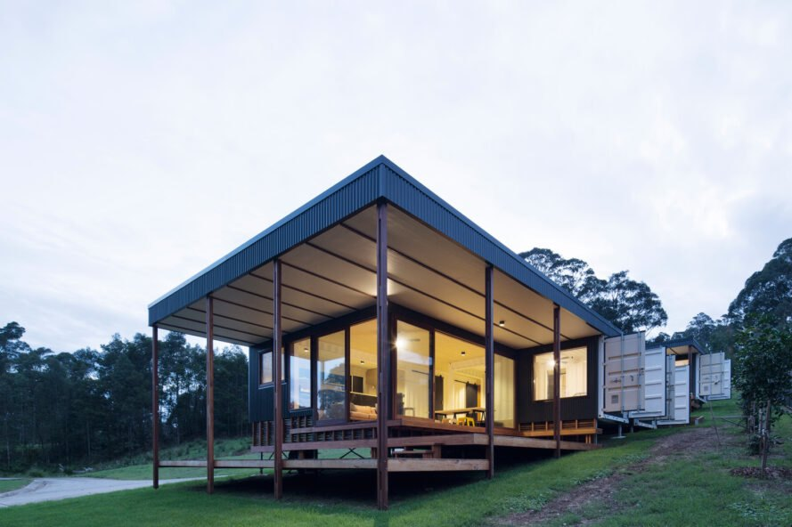 shipping container turned into a home with large windows and a deck