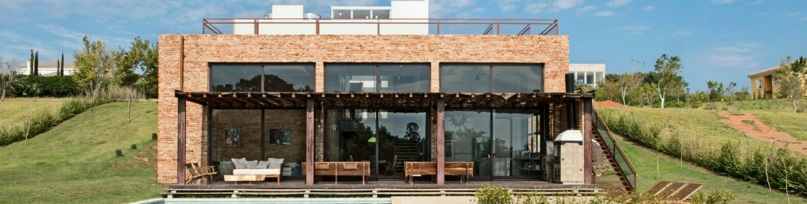 brick home with three large glass facades looking out over swimming pool