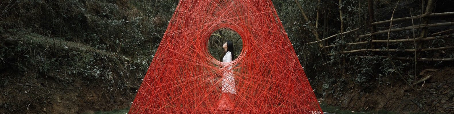 woman standing inside red woven triangle pavilion