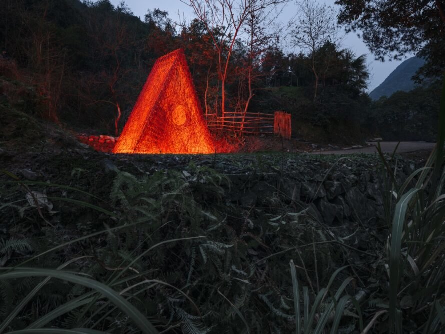 red triangular structure lit up at night