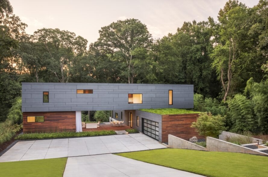 gray and wood home with green roof