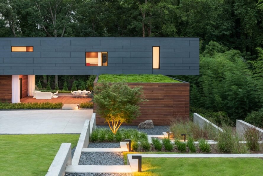 gray and wood home with green roof and gardens