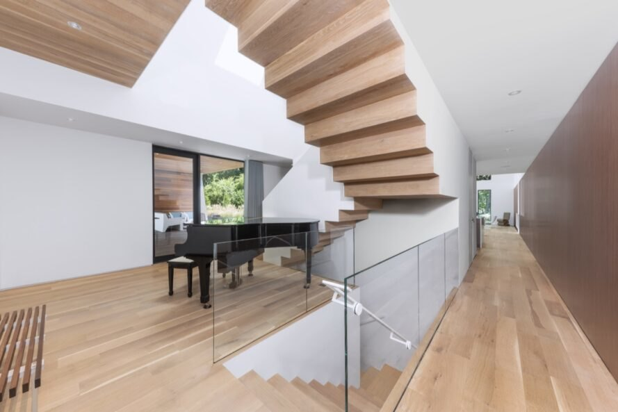 white living space with wood staircases and black piano