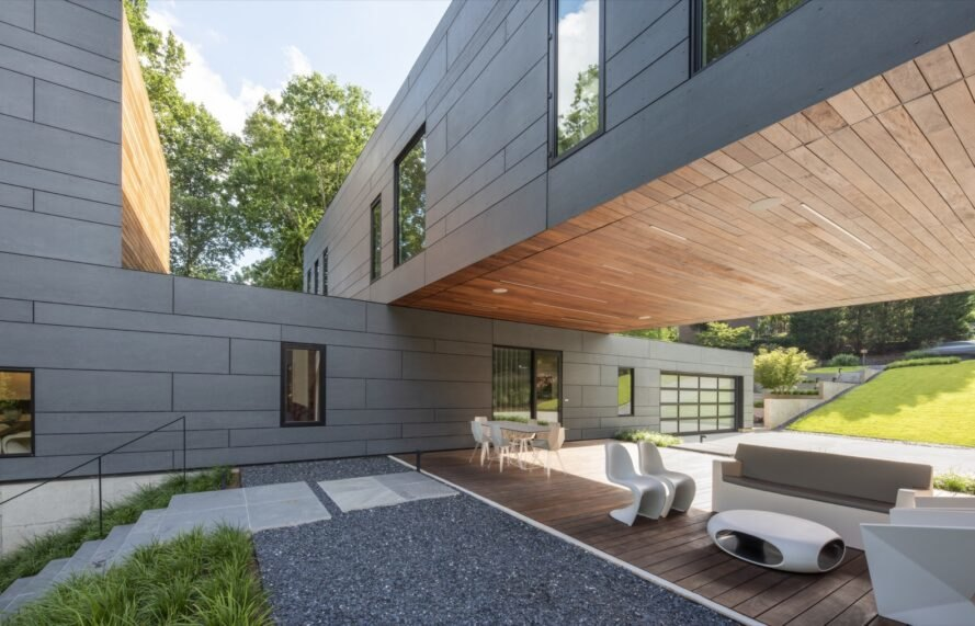 gray perpendicular volumes that form a covered outdoor patio