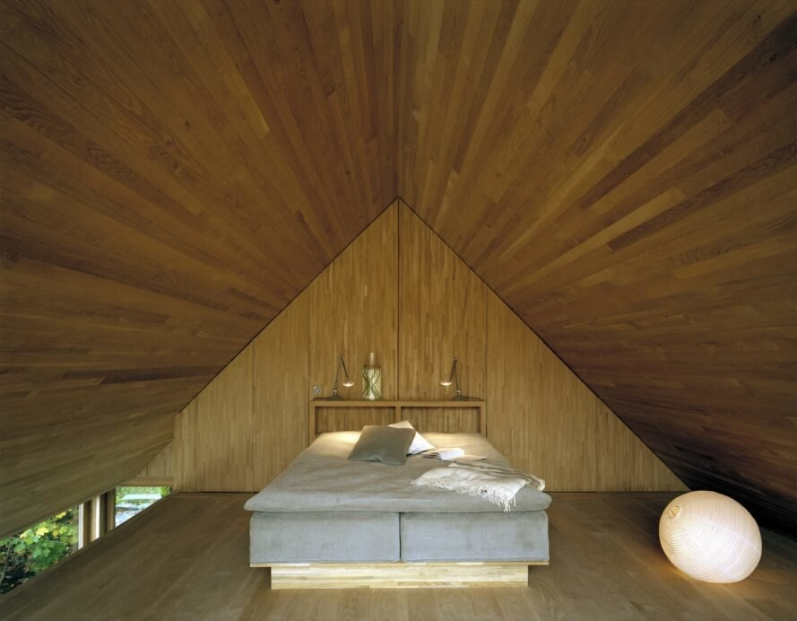 pyramid style bedroom with wooden walls shaped into a pyramid near the bed's headboard