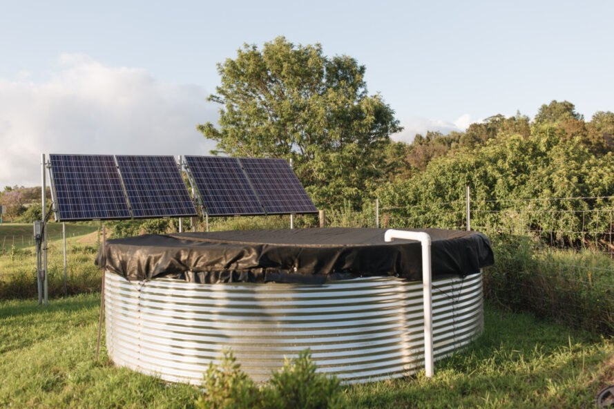 a large water tank with solar panels behind it