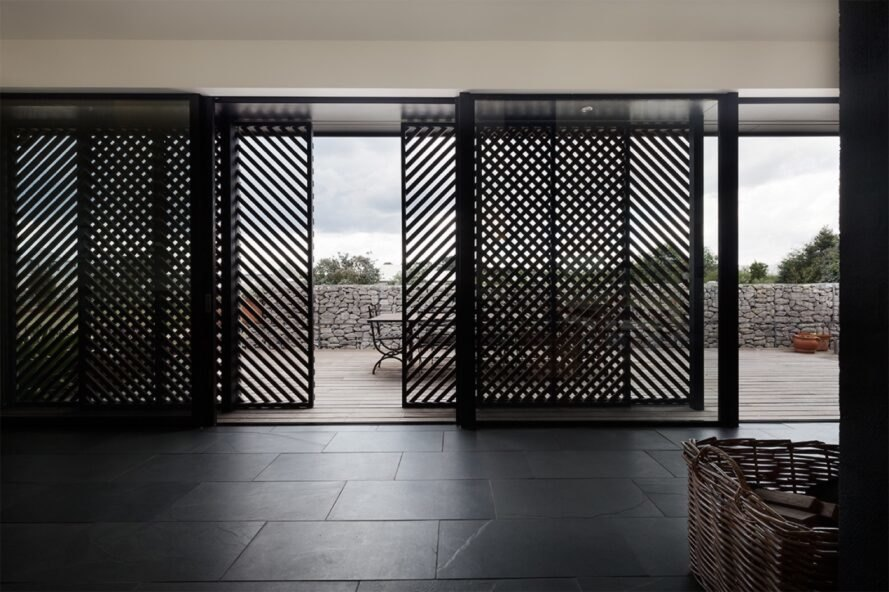 room with slatted screens opening to outdoor deck