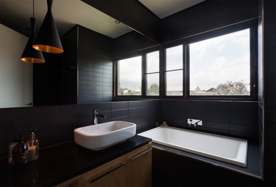 bathroom with black tiles and large white tub under a window