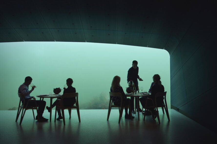 person serving food to people in room with glass wall revealing underwater views