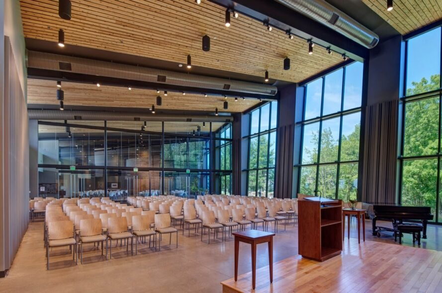 auditorium with wood ceilings, several wood chairs, a wood podium, and large glass windows