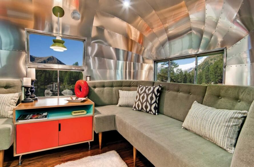 gray sofa and wood and red table inside an Airstream