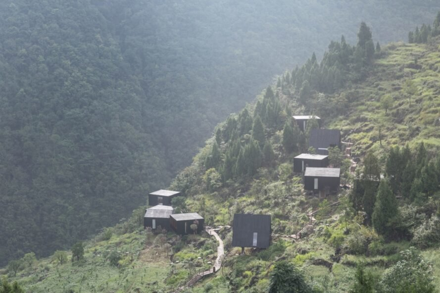 black wood cabins of different shapes and sizes on a green mountain