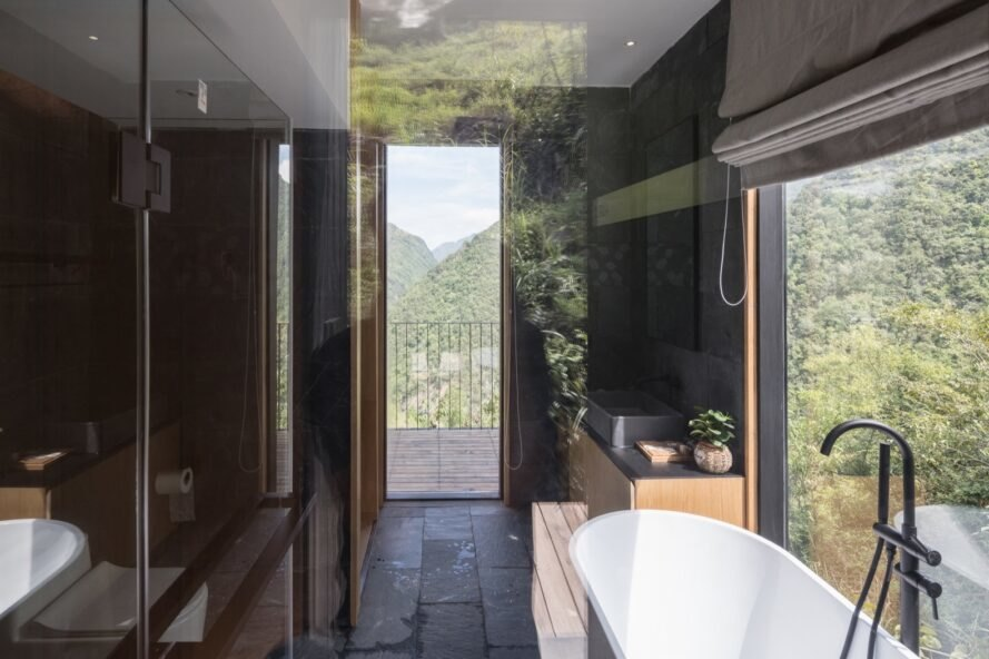 black bathroom with freestanding tub and door leading to outdoor deck