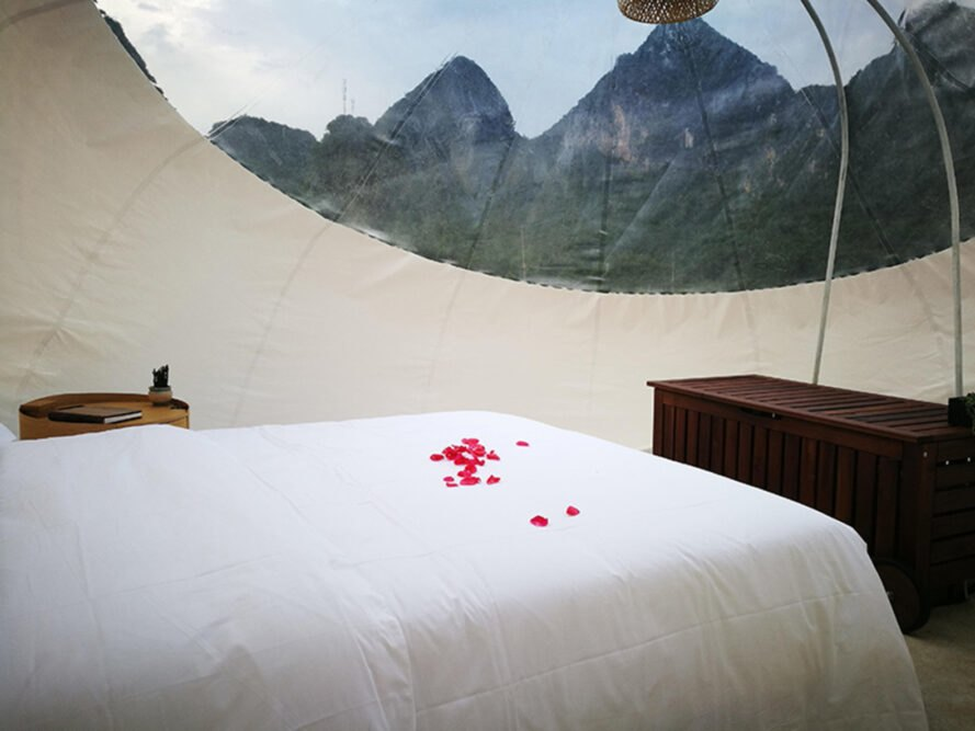bed with rose petals inside transparent bubble dome