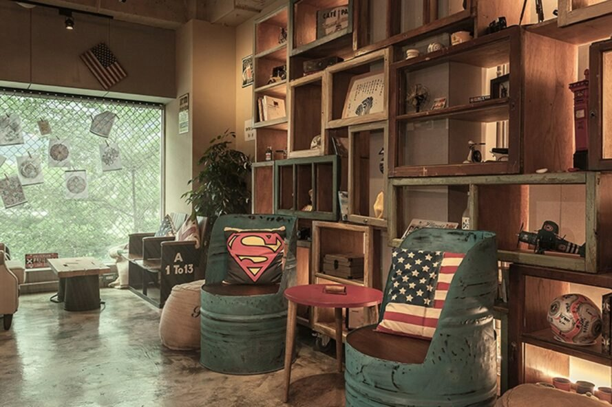 two seats made of metal barrels against a tall shelving system made from old window frames
