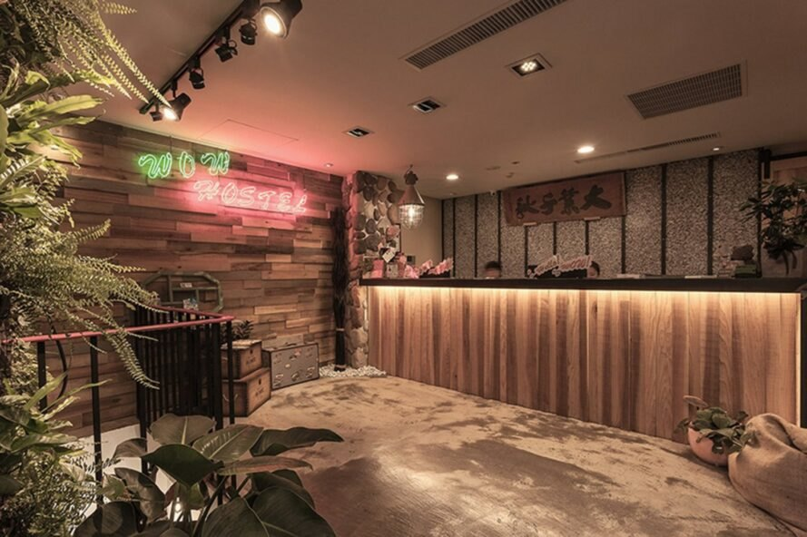wooden reception desk and wood wall with neon sign that reads Wow Hostel