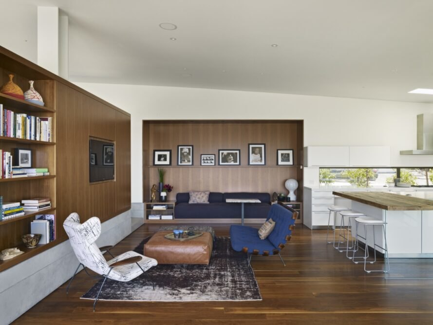 living room area of the home with wood flooes and accents on walls with white and blue couches