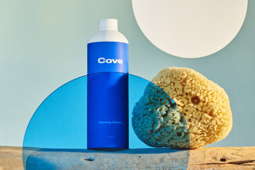 biodegradable water bottle on driftwood beside a natural sponge