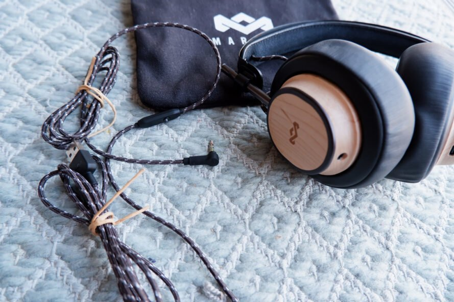 wood headphones beside braided cord and small black bag