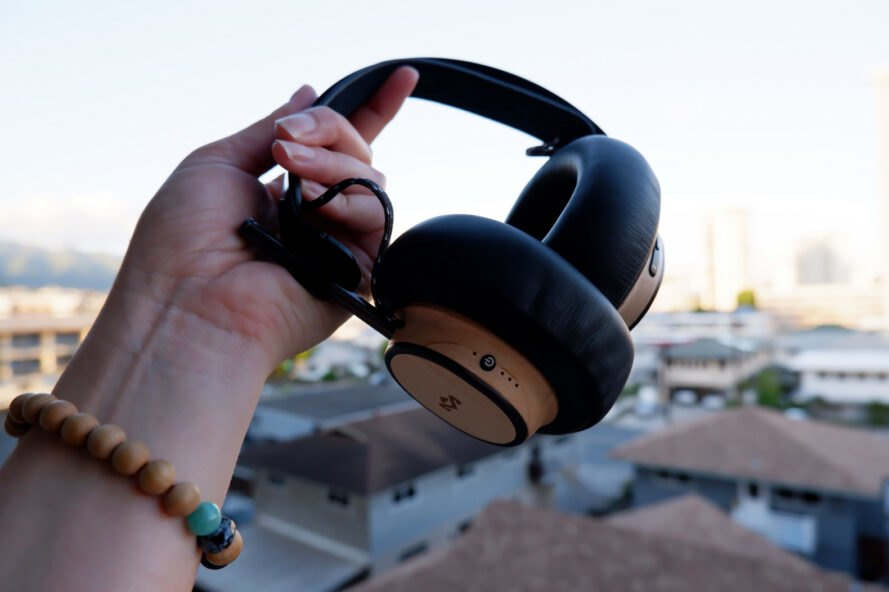 hand holding wood headphones with city in background