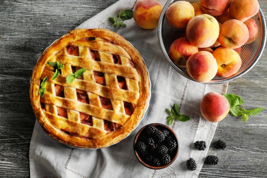 peach and blackberry pie next to bowl of blackberries and peaches