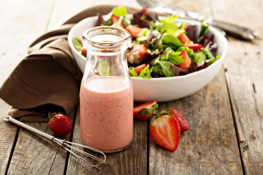 strawberry salad dressing in glass bottle next to salad