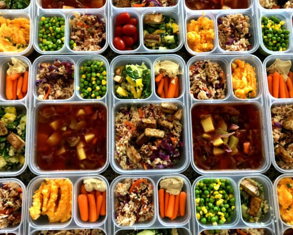 several plastic containers filled with plant-based foods