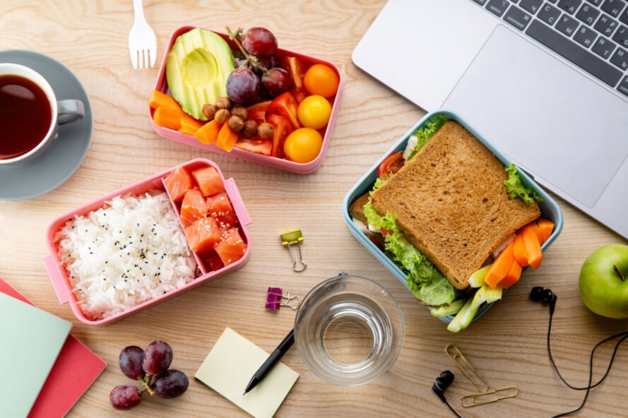 desk with containers of veggies, rice and a sandwich
