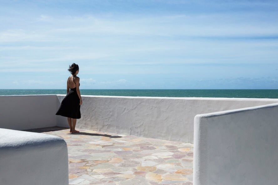 woman stands on home's roof during a sunny day looking out onto the ocean