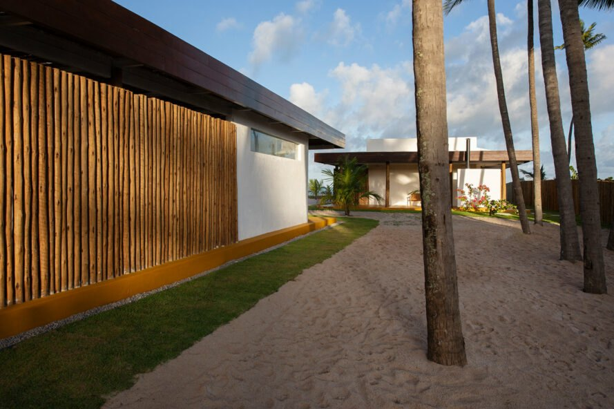 exterior of beach house with exposed twigs near palm trees and sand