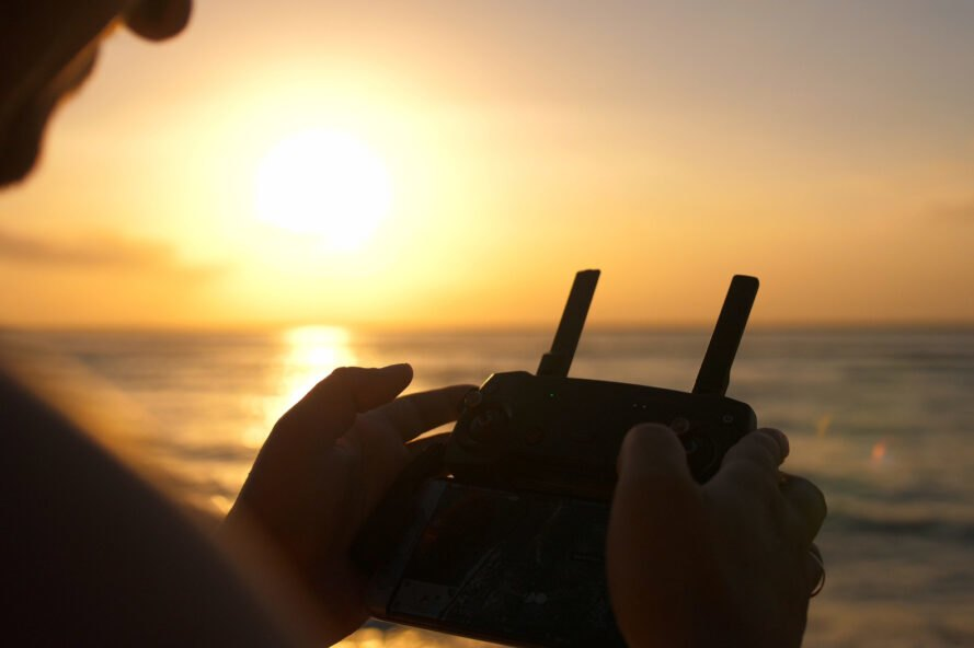 person holding drone controls at beach during sunset