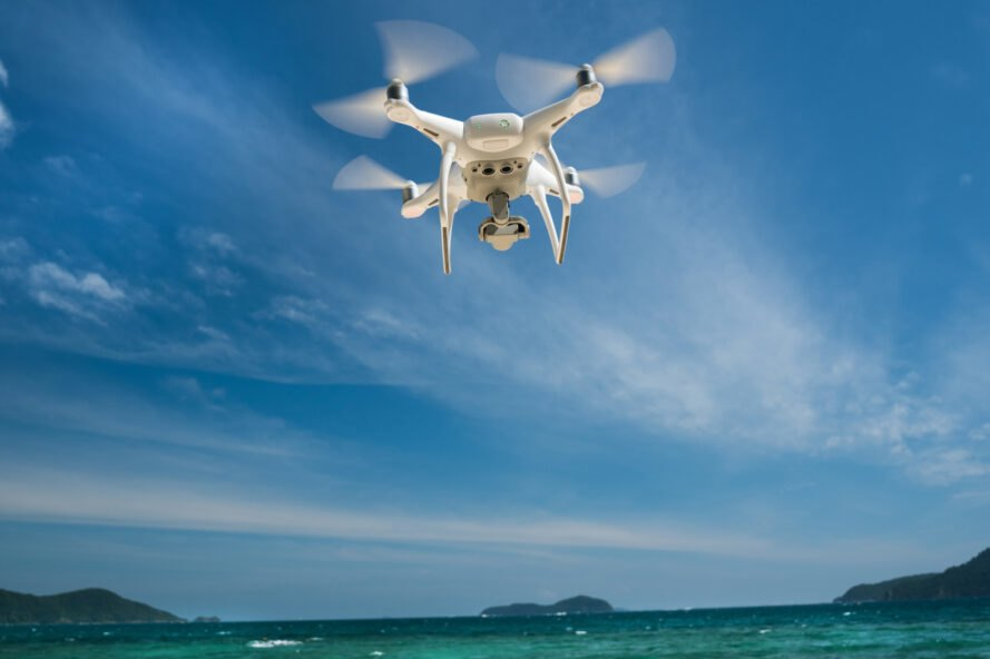 white drone in blue sky above clear ocean waters