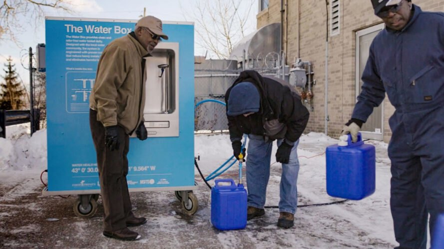 people filling blue water jugs at a blue water station